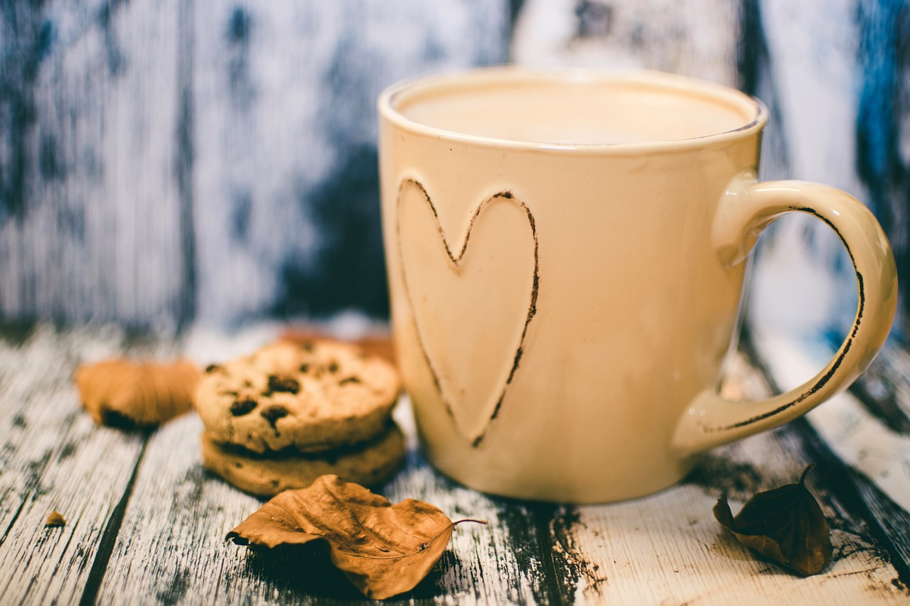 Photo of a mug with a love heart on it filled with coffee next to some leaves and cookies on a wooden backdrop